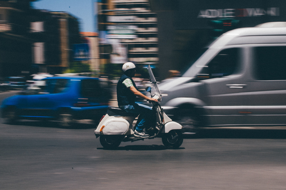 A man in Palermo, Sicily rides his moped through a hectic intersection. The streets of Palermo are always packed, with cars and bikes bustling in every direction at high speeds.