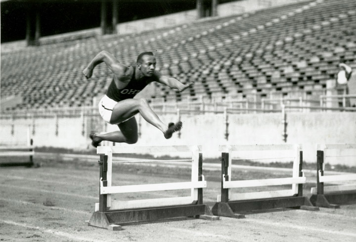 Jesse Owens jumping over a hurdle during practice at Ohio Stadium, side view, 1936