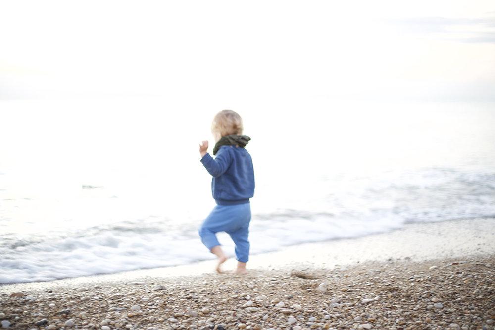 rowan picking stones running beach.jpg