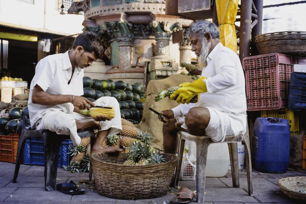 Preparing fresh pineapple for sale in Mumbai's Crawford Market