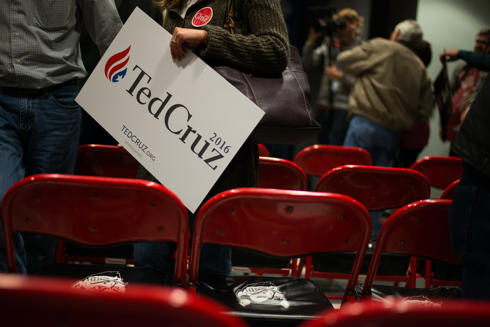 A woman carries a Ted Cruz campaign sign after Cruz addressed voters at Lamoni High School in Lamoni, Iowa, on Nov. 28, 2015.