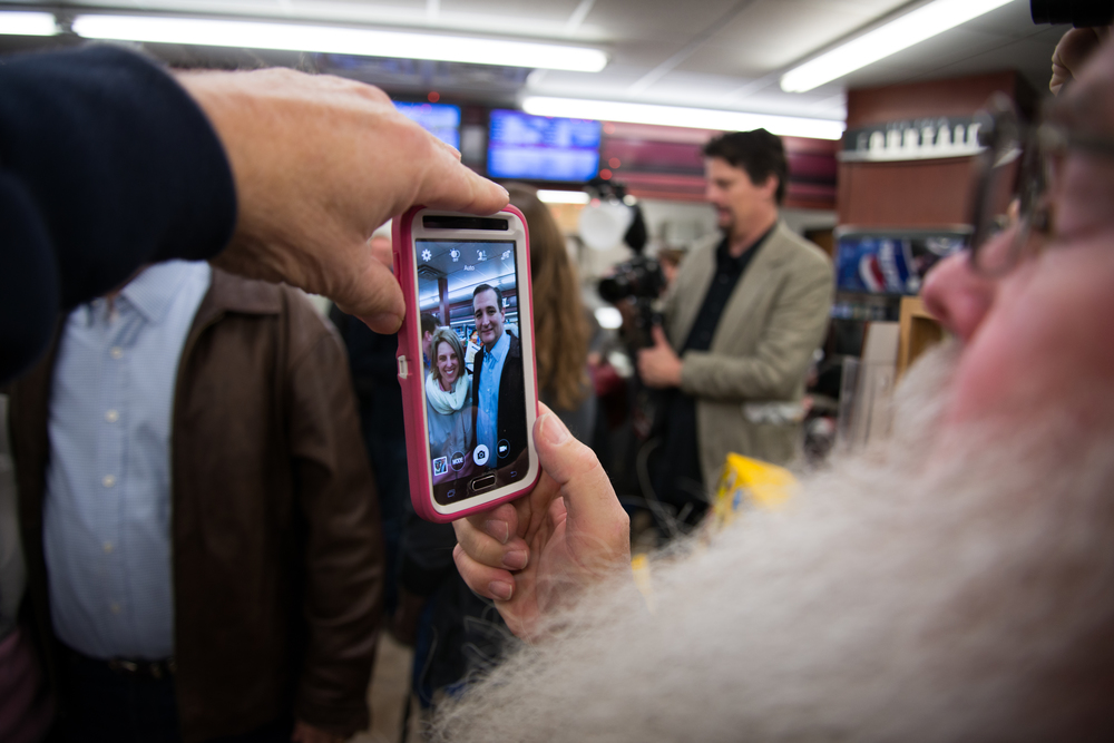 Republican presidential candidate Ted Cruz is seen through a cellphone screen as he poses for a photograph with a voter during a campaign stop at Casey's General Store, in Tama, Iowa, on Nov. 29, 2015.