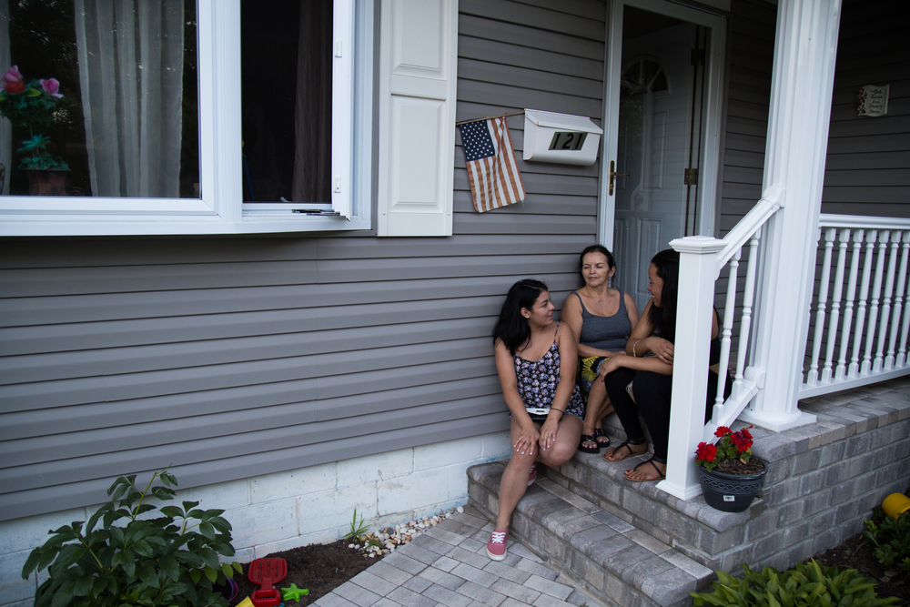 Eliana Sabogal, 18, (from left), her grandmother Luz Sanabria, 63, and her friend Natacha Castillo, 19, sit on the porch of Sabogal's family home in Southampton, NY, on August 3, 2015. Saboga works at a McDonald's in the summer to earn money that helps sustain her family in the winter.