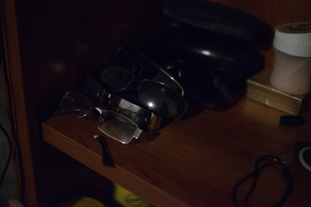 Several pairs of glasses sit on a bookshelf in Denis Reyes' bedroom in his mother's Bronx apartment, where he lived.