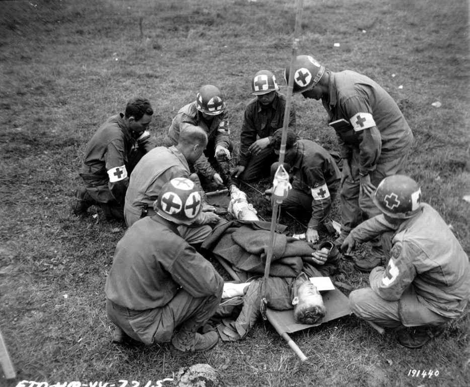 Medical team at work during the Battle of Normandy, World War II and utilizing an IV