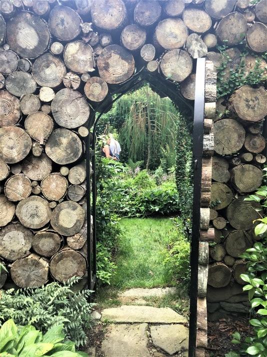 The log wall frames a view into a garden of green.