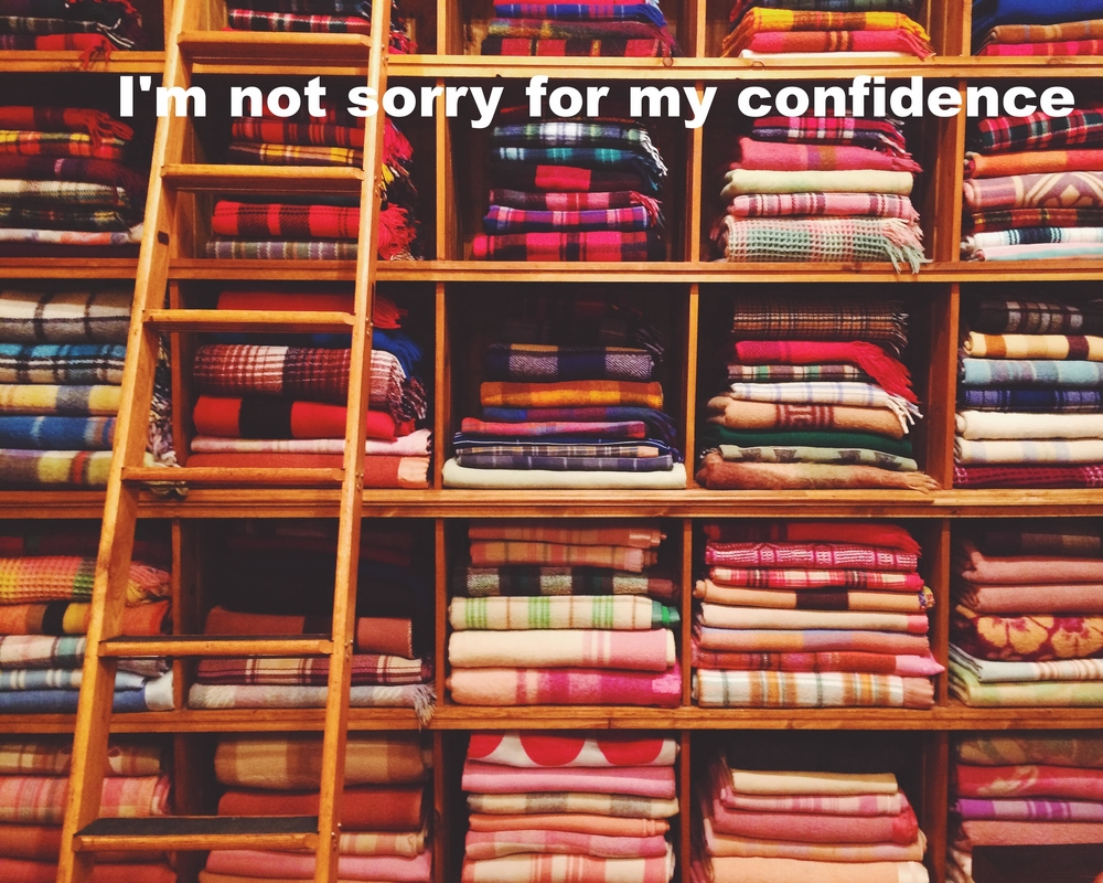 "Kirsten January 4 2016 Image of shelves with many folded colorful blankets. ""I'm not sorry for my confidence"" is overlaid."