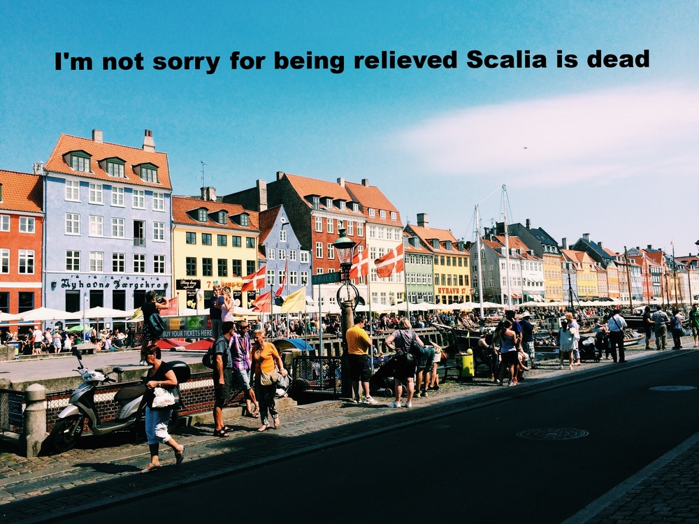 "Anonymous February 16 2016 Image of brightly colored houses along a canal. People walk along a cobblestone sidewalk, and there are Danish flags, vendors, and outdoor seating. ""I'm not sorry for being relieved Scalia is dead"" is overlaid."