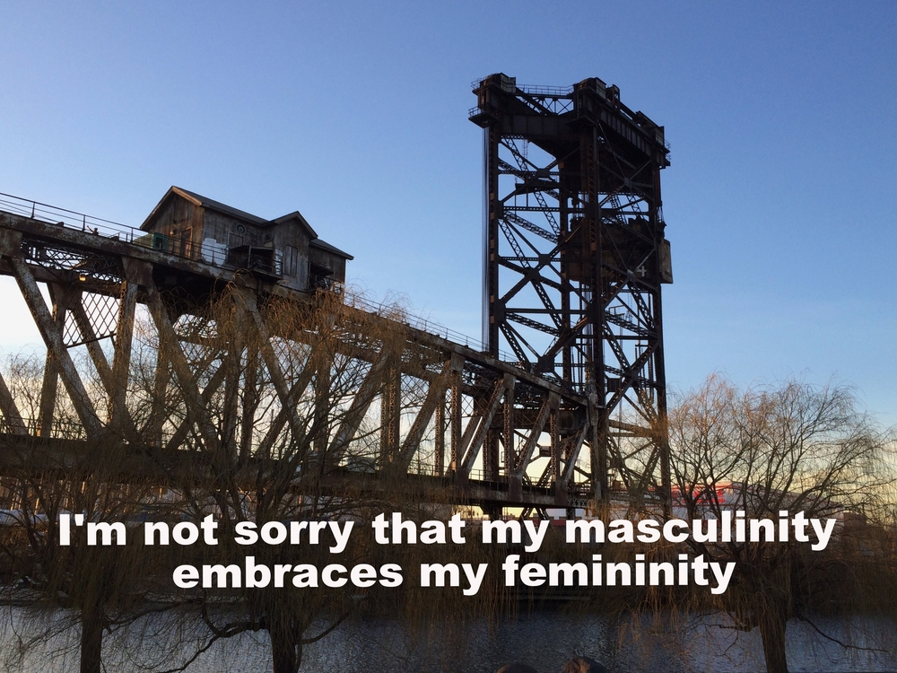 "Anonymous March 8 2016 Image of a steel bridge at sunset. At the top of the bridge is a small house-structure. The sky fades from blue to yellow. ""I'm not sorry that my masculinity embraces my femininity"" is overlaid."