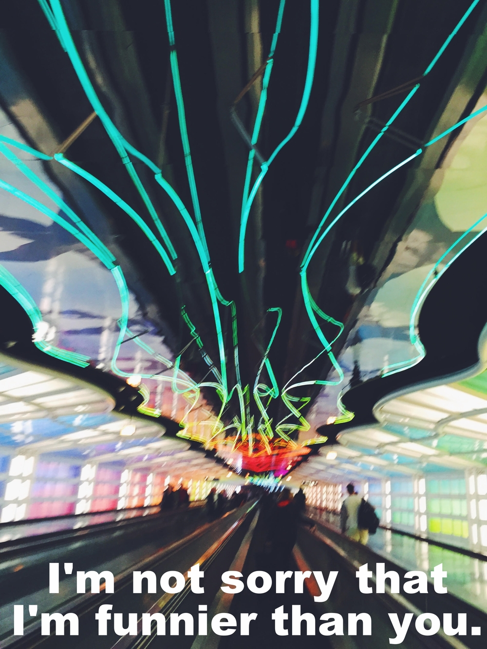 "Caroline March 24 2016 Slightly blurry image of a long hallway. There are several moving walkways running down the middle of the hallway, each with a few people on it. Rainbow colored lights span the length of the ceiling and are reflected in glass panels along the walls. ""I'm not sorry that I'm funnier than you"" is overlaid."
