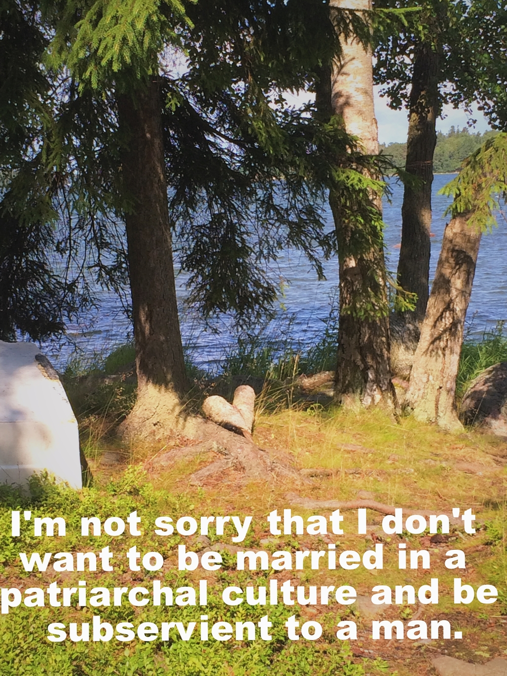 "Sarah April 26 2016 Grass and tree roots foreground an image of evergreen trees that overlook a lake. There is a heart-shaped rock or root at the base of one of the trees. ""I'm not sorry that I don't want to be married ina a patriarchal culture and be subservient to a man"" is overlaid."