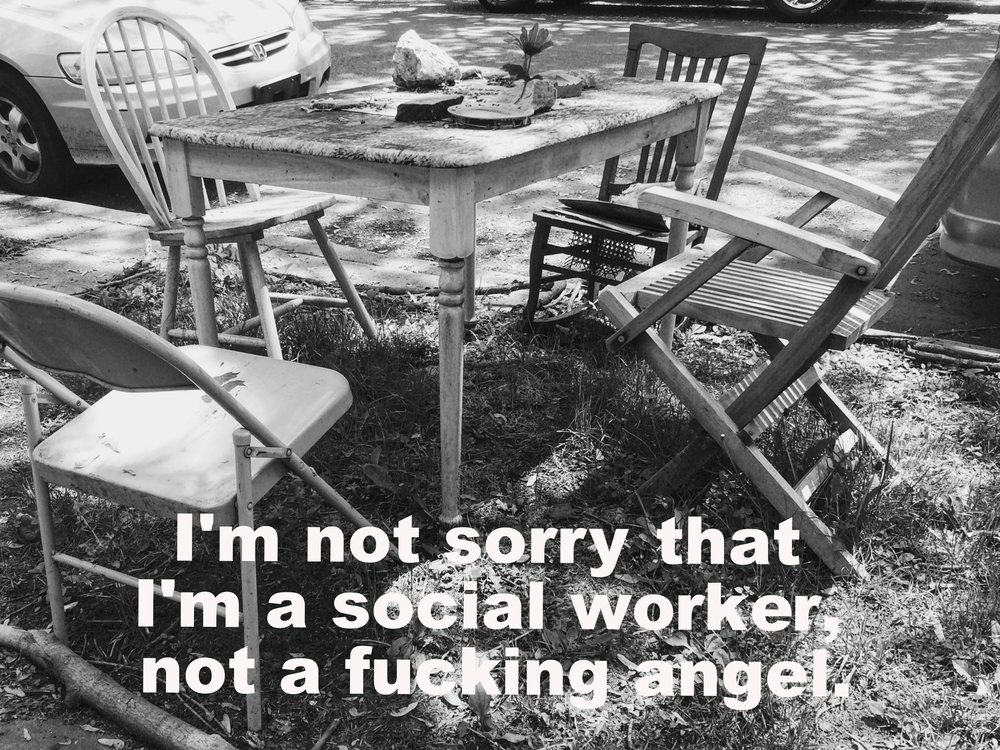 "Anonymous May 25 2016 Black-and-white image of a square wooden table, surrounded by four unmatching chairs on the grassy strip between the sidewalk and the street. There is a plate, a rock, and a flower on the table. ""I'm not sorry that I'm a sorry that I'm a social worker, not a fucking angel"" is overlaid."