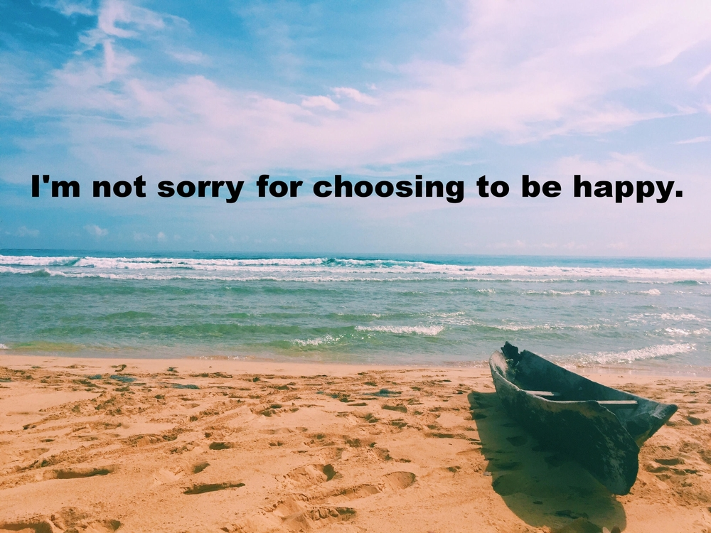"Anonymous June 6 2016 Image of the edge of the water on a beach. There are many footprints in the sand leading down to the water, which is greenish-blue and dotted with small waves. A hand-carved wooden canoe sits at the edge of the sand to the right of the frame. ""I'm not sorry for choosing to be happy"" is overlaid."