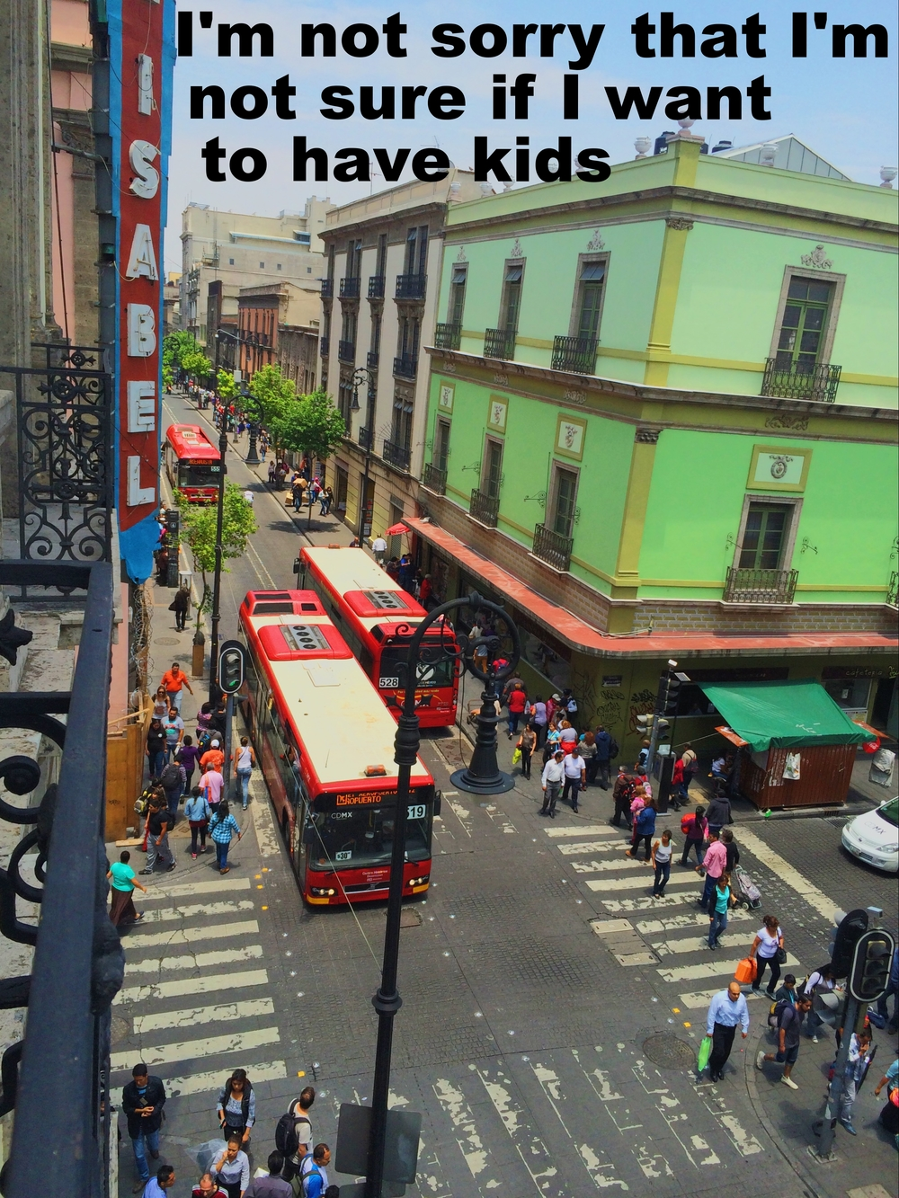 "Julie Ann May 26 2016 Image of a busy street taken from above. Pedestrians cross the street, and two large red buses pass one another in the intersection. ""I'm not sorry that I'm not sure if I want to have kids"" is overlaid."