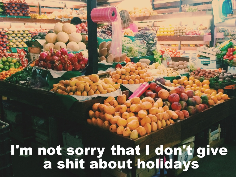 "Anonymous July 4 2016 Image of lots of colorful, whole fruits displayed at a market stall. ""I'm not sorry that I don't give a shit about holidays"" is overlaid."