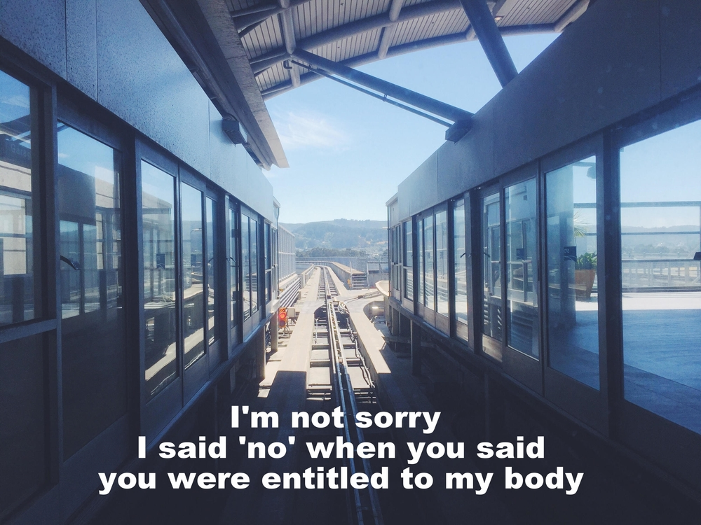 "Sam July 8 2016 Image of an elevated train track stretching into the distance between two walls of glass doors. The foreground is in shadow; in the distance the track stretches into sunshine. ""I'm not sorry I said 'no' when you said you were entitled to my body"" is overlaid."