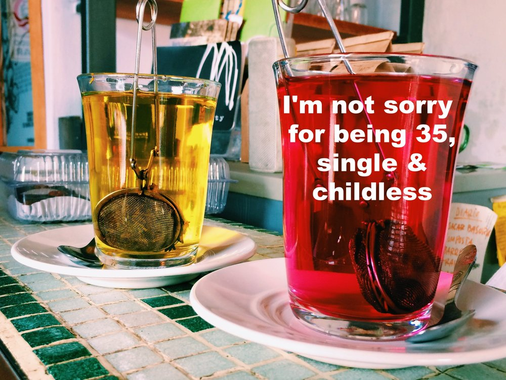 "Anonymous August 25 2016 Image of two cups of tea in clear glasses on a green and white tile countertop. They both have infusers steeping in them, and one is a bright pink, and the other is golden-yellow. ""I'm not sorry for being 35, single & childless"" is overlaid."