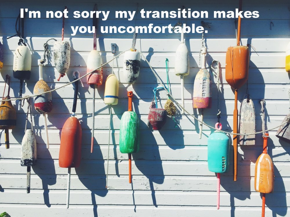 "Anonymous August 23 2016 Image of many colorful buoys hung against a white clapboard wall, in bright sunlight. ""I'm not sorry my transition makes you uncomfortable"" is overlaid."