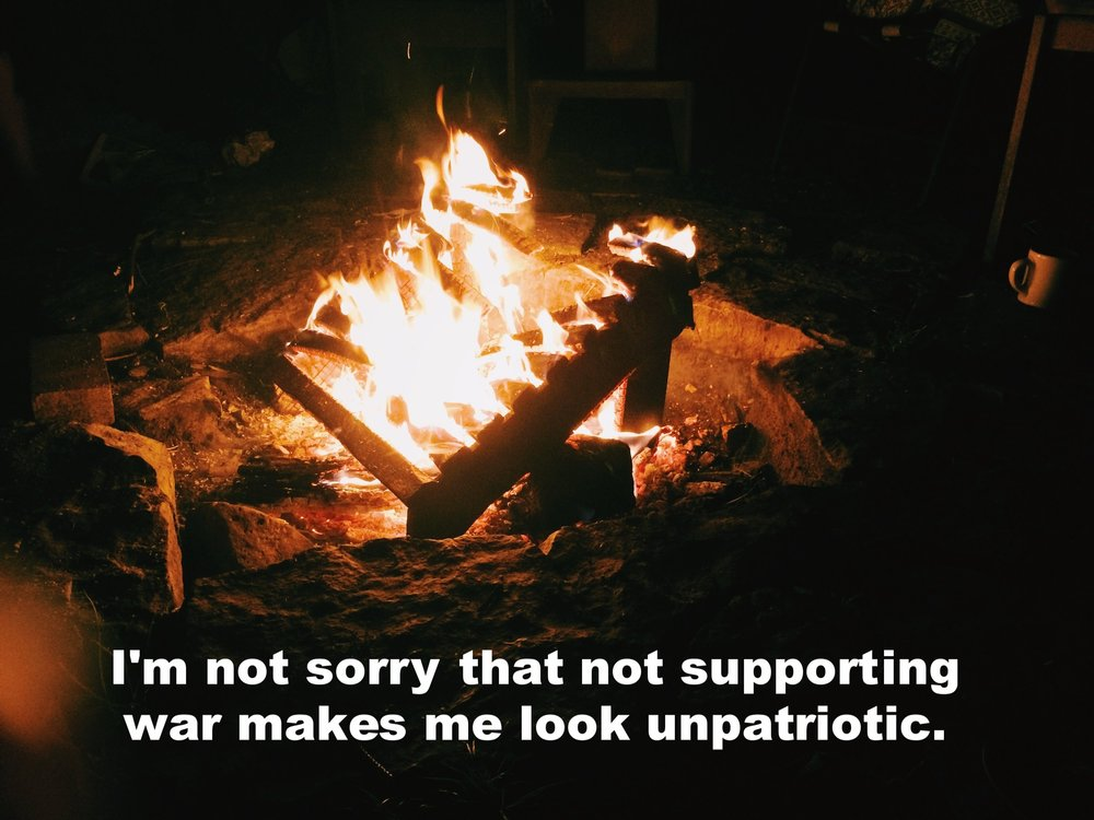"Tanner September 7 2016 Image of a fire in a fire pit at night. Flames light up wood furniture burning in the fire, as well as the stones surrounding it. ""I'm not sorry that not supporting war makes me look unpatriotic"" is overlaid."