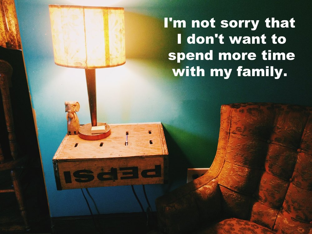 "Anonymous November 11 2016 Image of a table lamp on a wooden crate, lighting up a teal wall and orange quilted armchair. ""I'm not sorry that I don't want to spend more time with my family"" is overlaid."