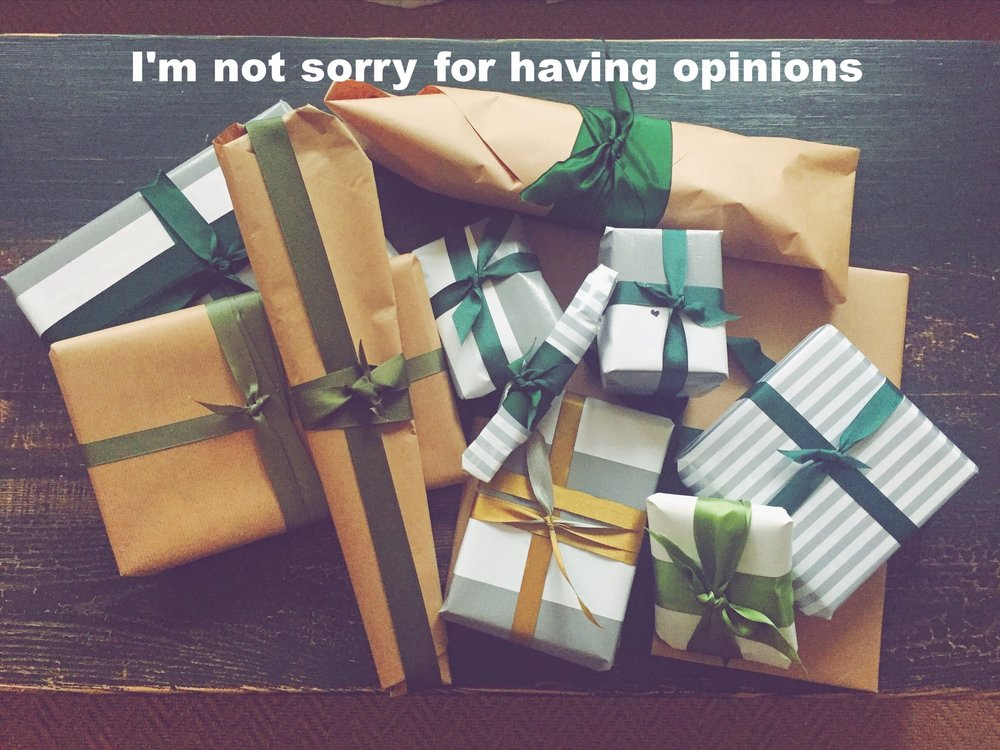 "Anonymous December 21 2016 Image of many packages wrapped in brown paper or silver and white striped paper and tied with green ribbons. ""I'm not sorry for having opinions"" is overlaid."