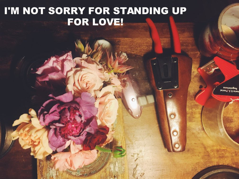 "Anonymous January 22 2017 Image of an arrangement of flowers in various shades of pink set on a table that also holds metal clippers in a leather sheath, and a roll of packing tape. ""I'm not sorry for standing up for love!"" is overlaid."