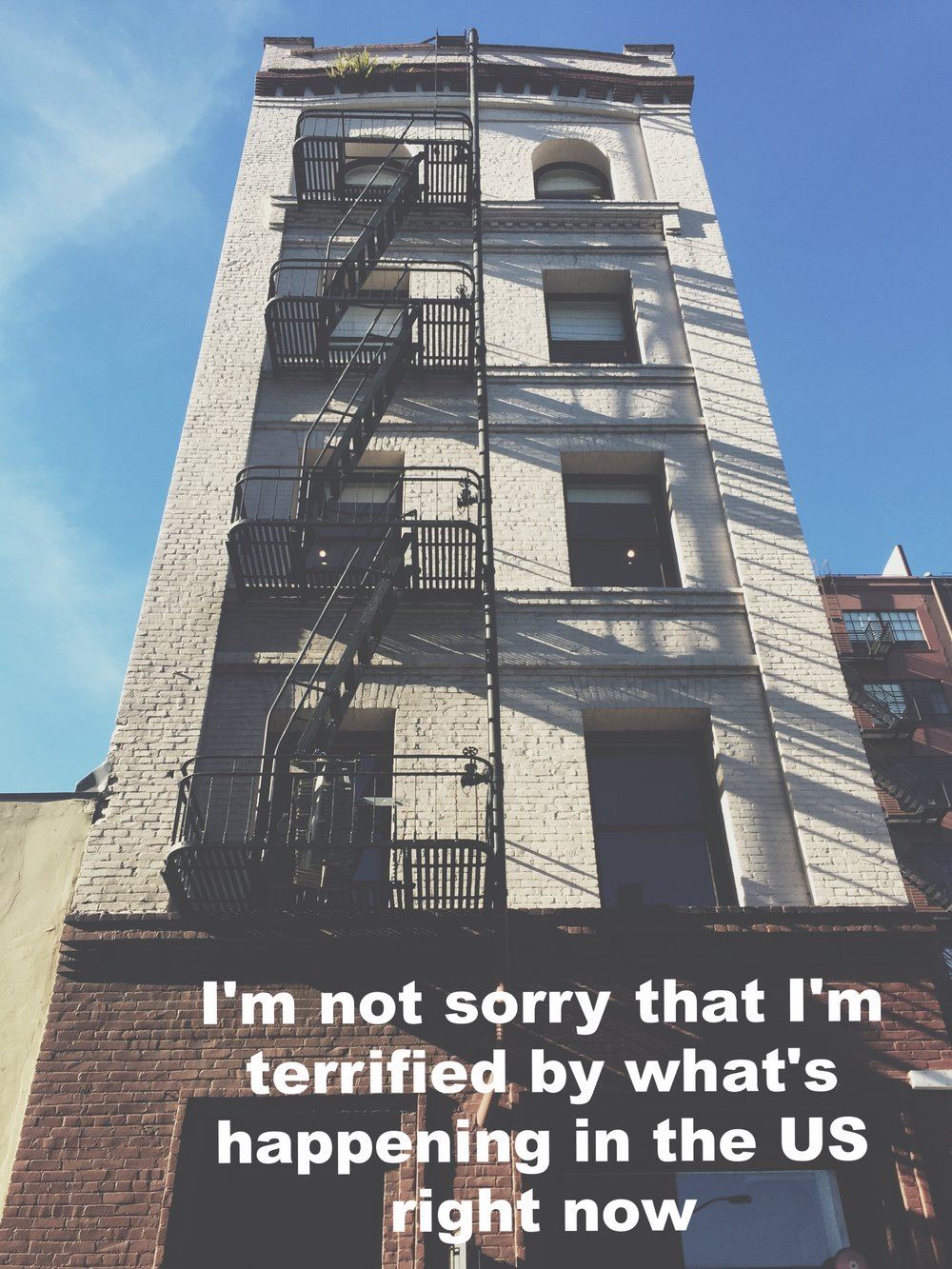 "Sarah (sasemon) January 31 2017 Image of a tall white brick building with wrought-iron fire escapes on one side, shot from below against a bright blue sky. ""I'm not sorry that I'm terrified by what's happening in the US right now"" is overlaid."