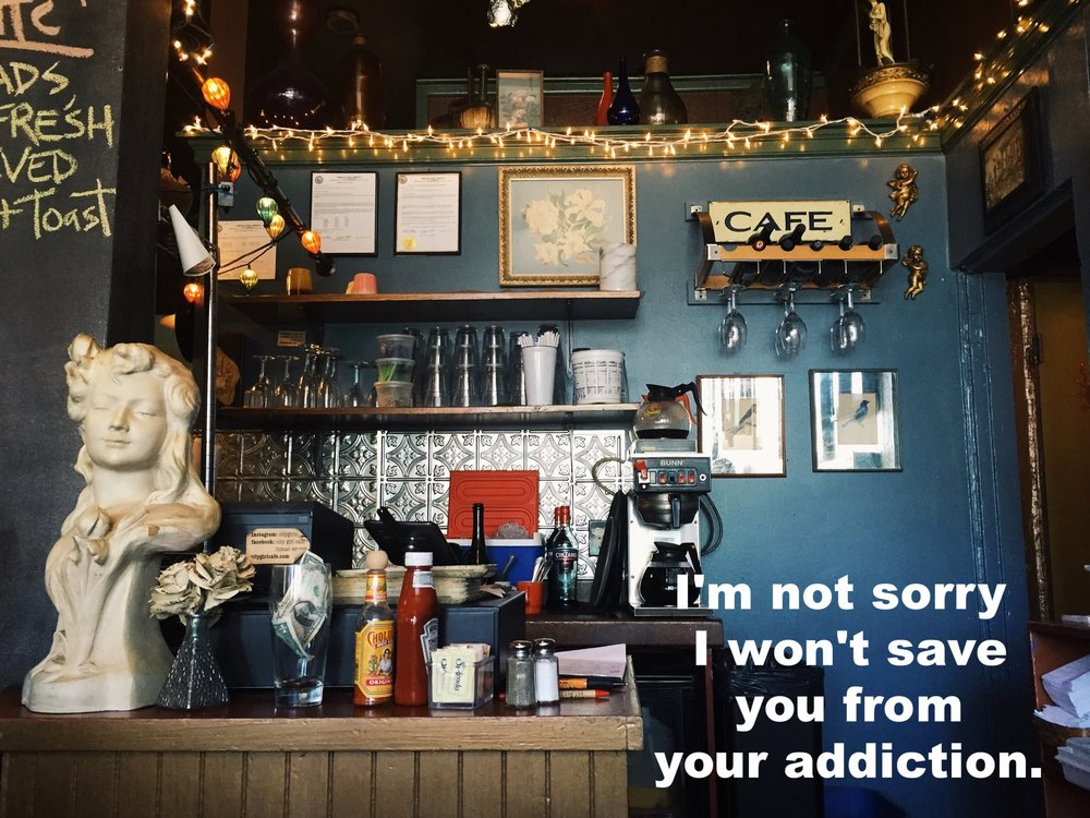 "Anonymous February 13 2017 Image of a cafe counter with condiments, a coffee maker, and various kitschey decorations including a white bust statue. The wall behind the counter is teal, and white twinkle lights line the upper border of the wall. ""I'm not sorry I won't save you from your addiction"" is overlaid. Photo credit: Lindsay Kopit"