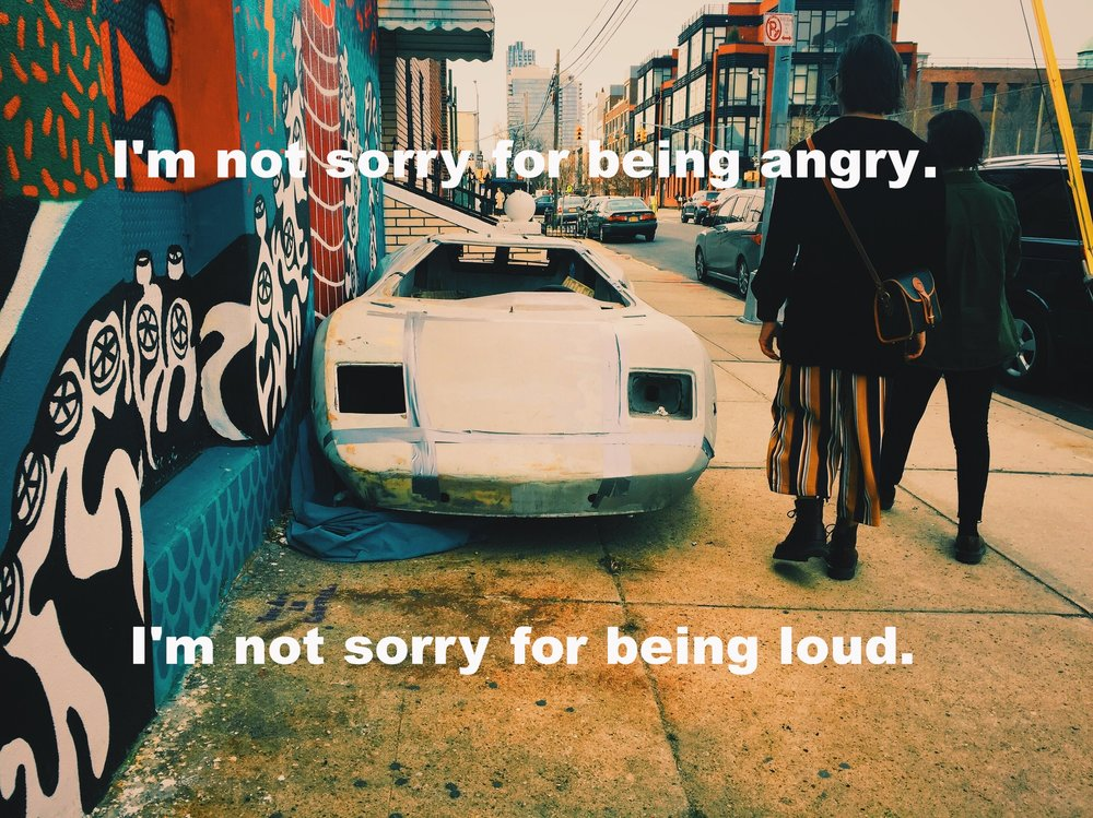 "Leah February 14 2017 Image of an unworking and taken-apart white sports car on the sidewalk against a colorful mural. Two people, one with baggy striped pants, both carrying shoulder bags, walk by, backs to the camera. ""I'm not sorry for being angry. I'm not sorry for being loud"" is overlaid. Photo credit: Lindsay Kopit"