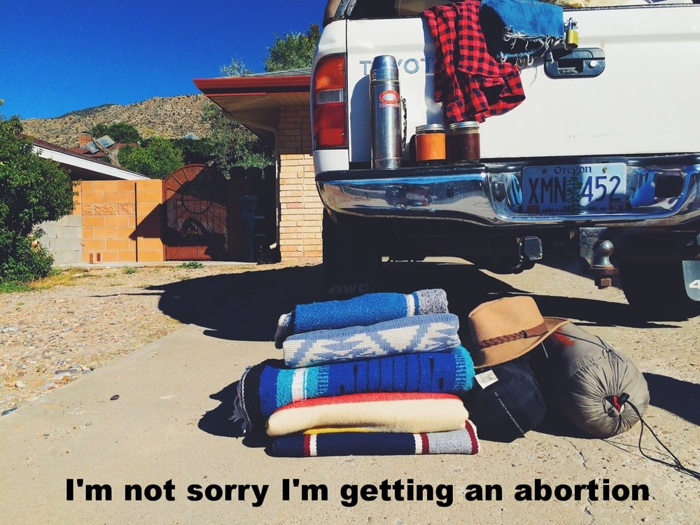 "Anonymous March 18 2017 Image of the back of a pickup truck. A thermos sits on the bumper, and a pile of neatly folded, colorful blanks in on the ground in the foreground. ""I'm not sorry I'm getting an abortion"" is overlaid."