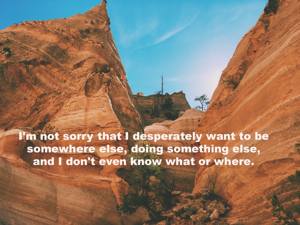 """Anonymous March 26 2017 Image of huge brownish-red rock formations streaked with white against a blue sky.""""I'm not sorry that I desperately want to be somewhere else, doing something else, and I don't even know what or where"""" is overlaid. Photo by Nino Cipri"""