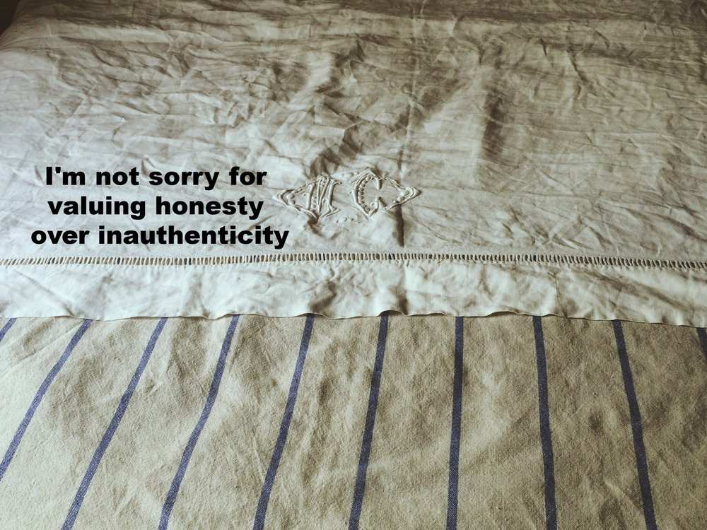 "Anonymous April 13 2017 Image of a bed made up with a tan and blue striped linen blanket and a white monogrammed sheet, which is wrinkled. ""I'm not sorry for valuing honesty over inauthenticity"" is overlaid."