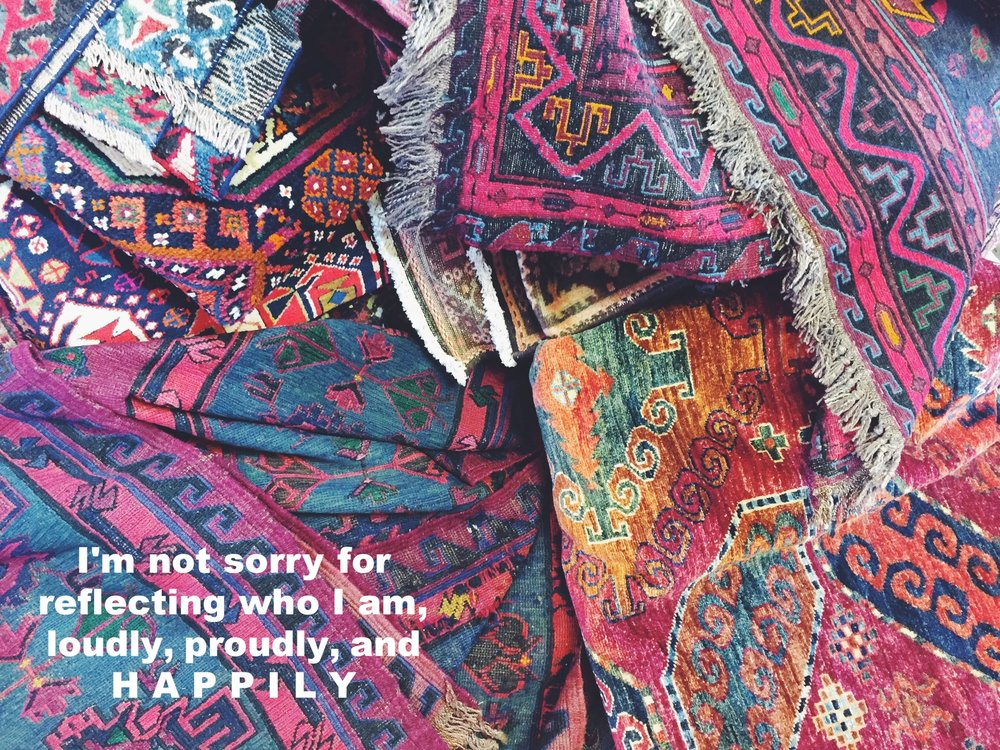 "E.3 April 30 2017 Image of many colorful rugs haphazardly piled on each other. ""I'm not sorry for reflecting who I am, loudly, proudly, and HAPPILY"" is overlaid."