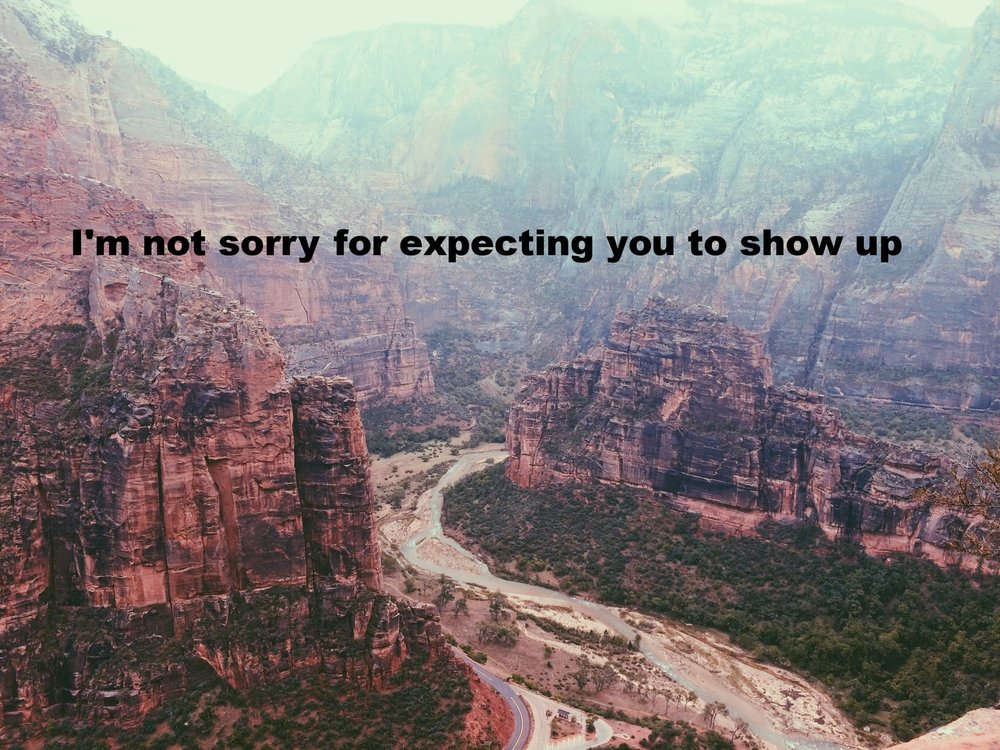 "Anonymous May 24 2017 Enormous red-brown mountains frame the picture, with a stream flowing through a valley running through the center. Mountains fade in the distance. ""I'm not sorry for expecting you to show up"" is overlaid."
