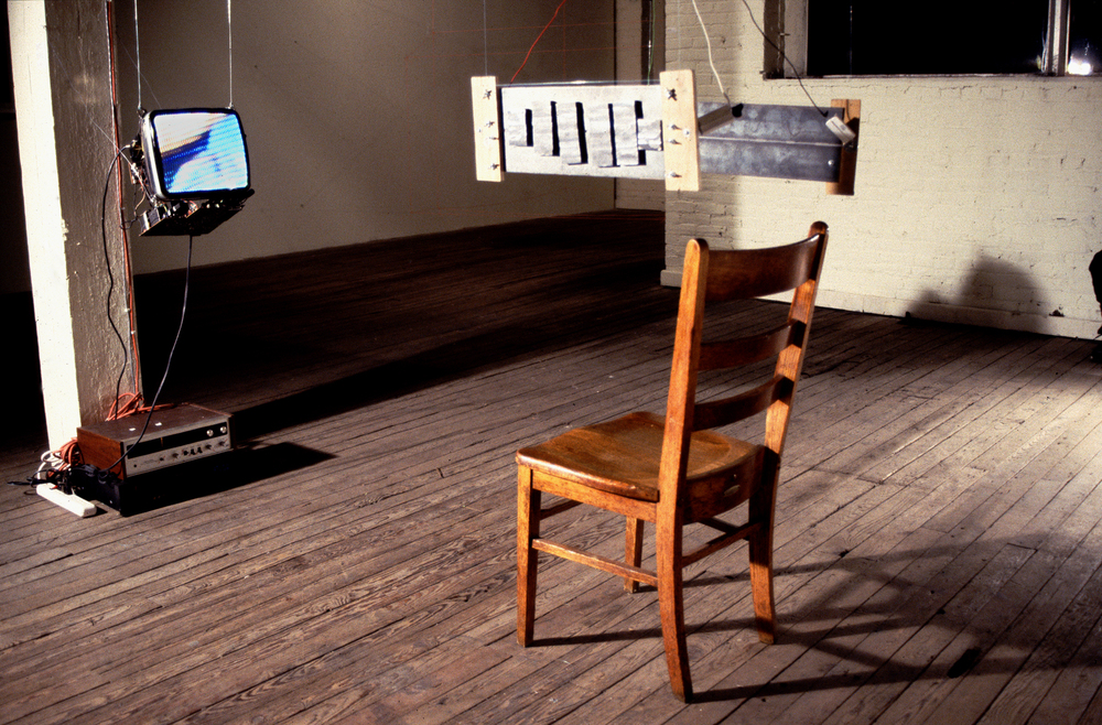 (installation view) Deconstructed Corruption (Static) 1999 deconstructed television, VCR, video loop, audio amp, audio loop, chair, constructed speakers, various cables, viewers (seated in chair) dimensions vary * this was a collaboration piece with artist Andrew Tomasulo