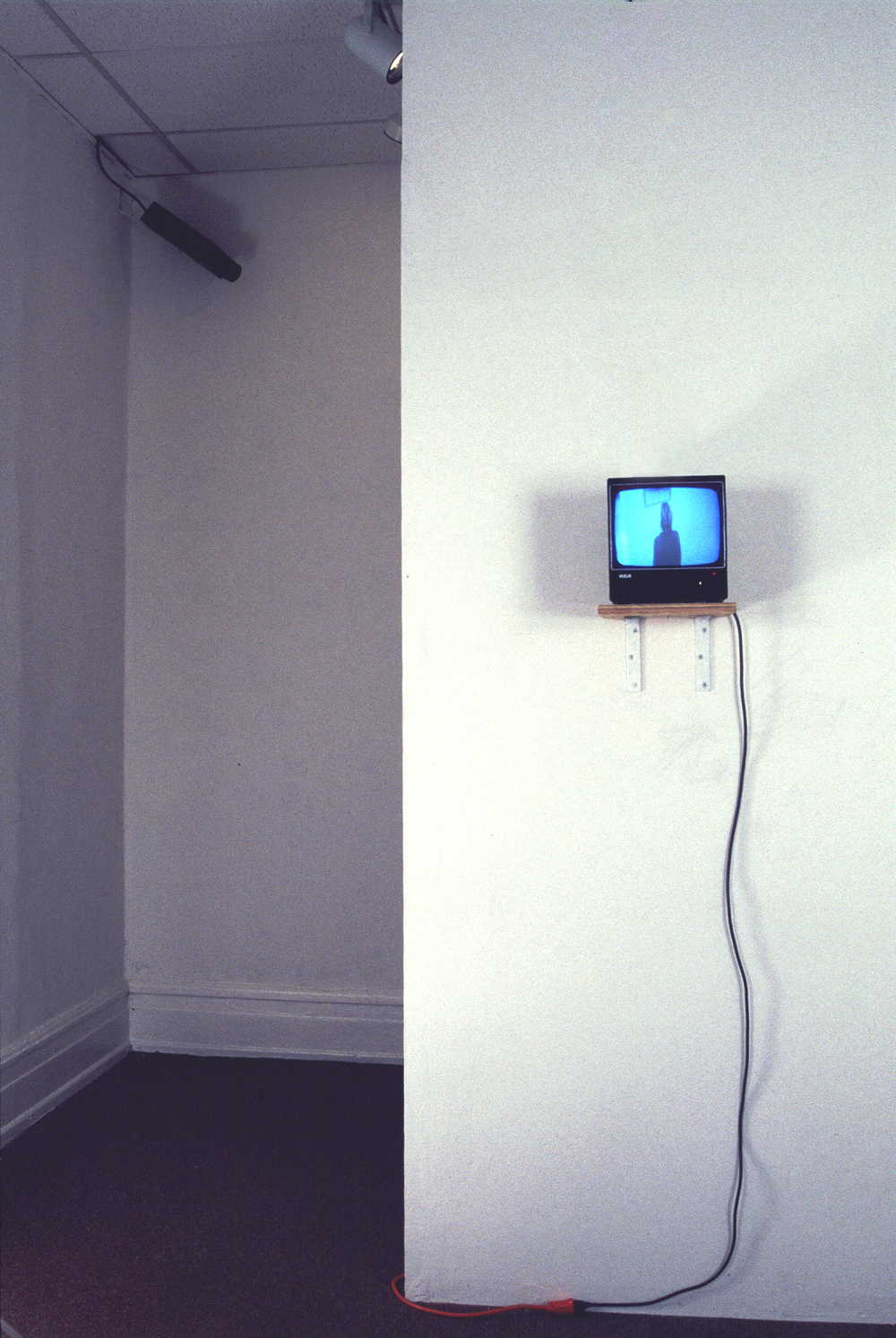 (installation view, front view) Room Shift 1997 surveillance equipment, custom-made two part wooden bench, custom-made two part wooden frame, color photograph and various cables & cords dimensions vary