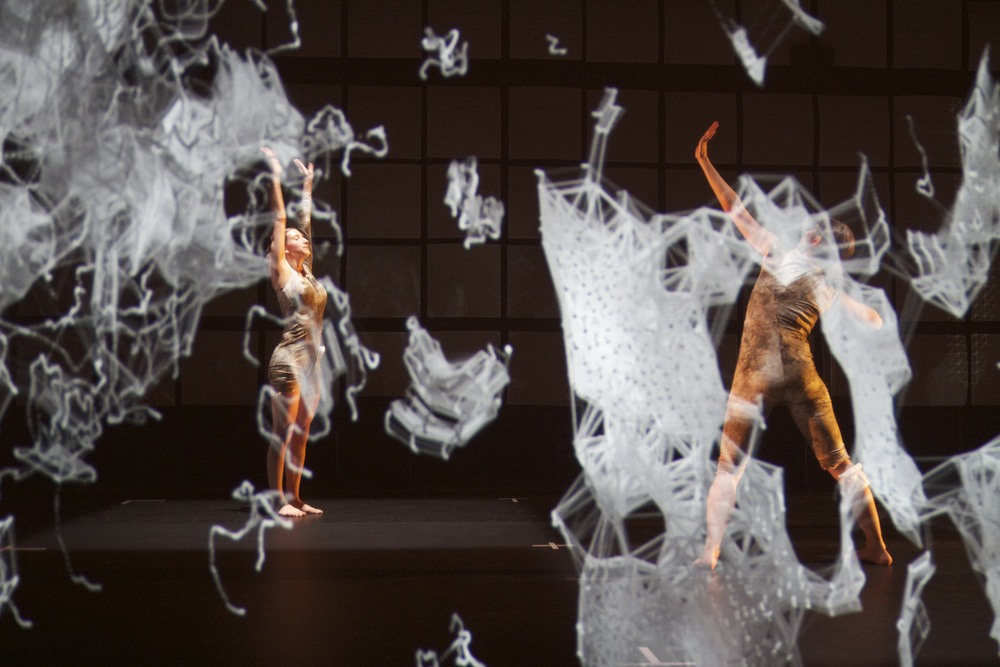 Dancers wearing the Xth Sense designs in a performance. The projected visuals and audio come from biosignals detected by the wearables.