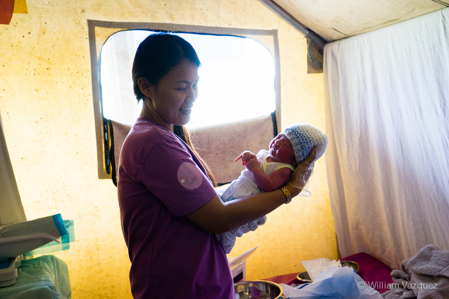 Midwife holding a newborn baby at Bumi Sehat Foundation clinic in Dulag, Philippines