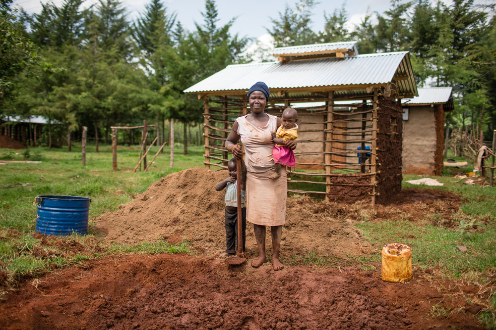 A Kenyan women building her new kitchen by hand, with a design that will reduce smoke.
