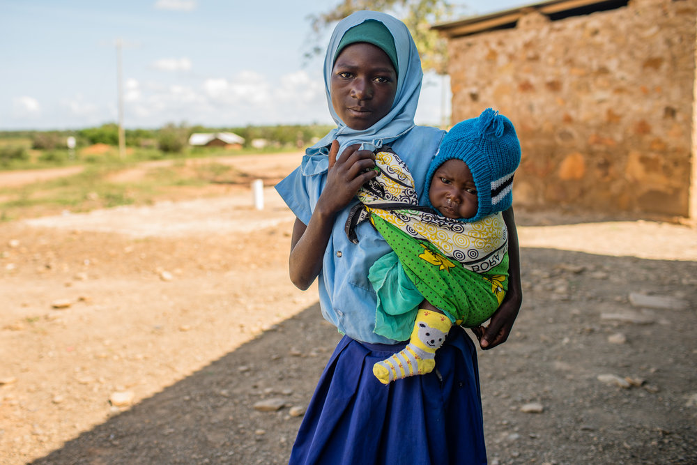 A young girl with her little brother waiting for her mother at a clinic outside Mombassa, Kenya.