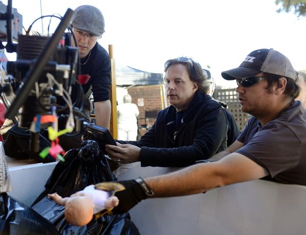 From left: director of photography Laffrey Witbrod, director Charles Dye and production designer Greg Eakins use a doll to set up a shot in a Dumpster for a movie being filmed Tuesday in the east alleyway, off Third Avenue, in downtown Longmont.  (Lewis Geyer / Longmont Times-Call)