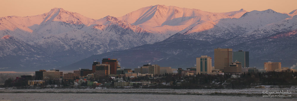 Downtown Anchorage with the Chugach Mountains behind her.