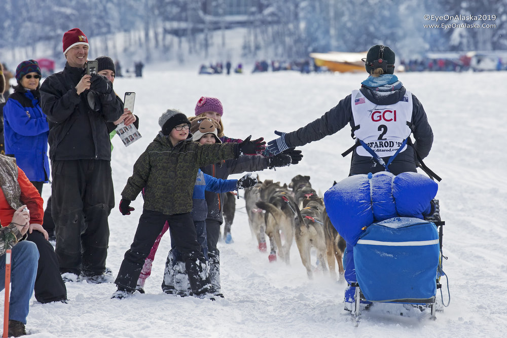 Anja Radano, the first musher to start, continues the tradition of high-fiving the kids as she passes the crowds.