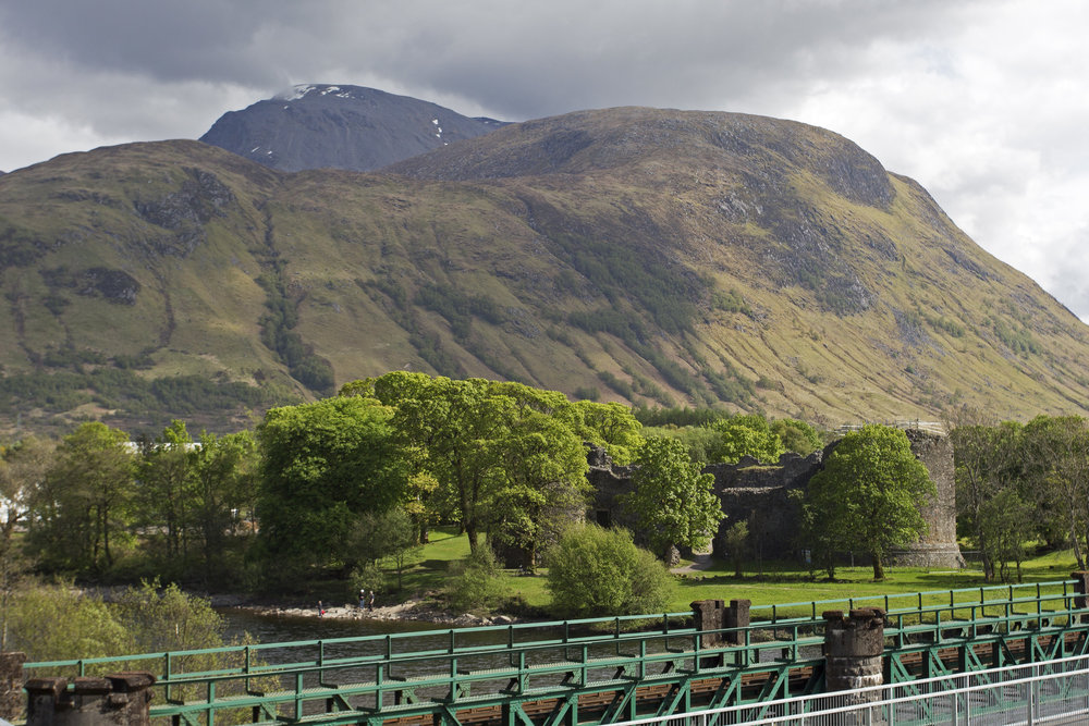 A view of Ben Nevis peaking out above the castle ruins.