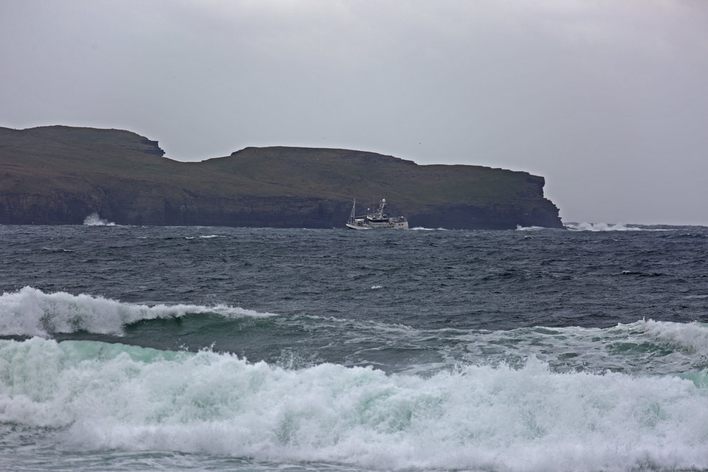 We watched this fishing boat get knocked almost on its side by a big wave.