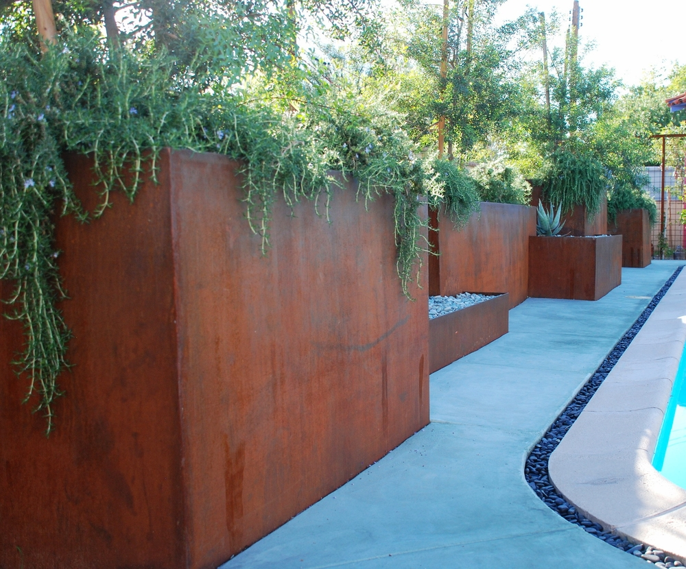 Jogged steel planters created dimensional interest along the back side of a pool.