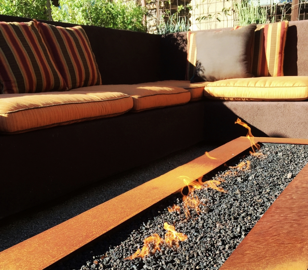 Metal fire feature surrounded by built-in banco seating.
