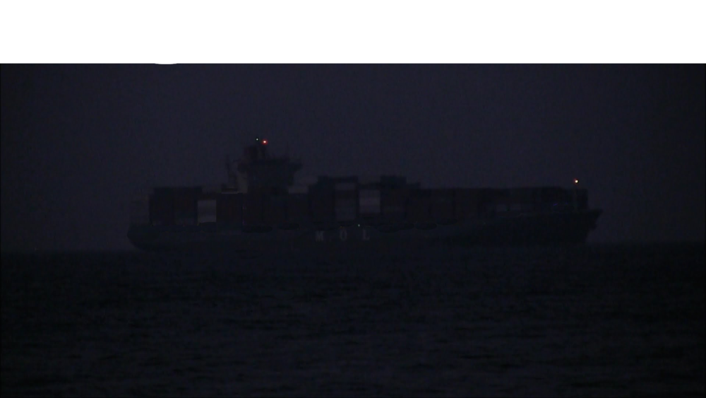 Container ships appearing out the dark