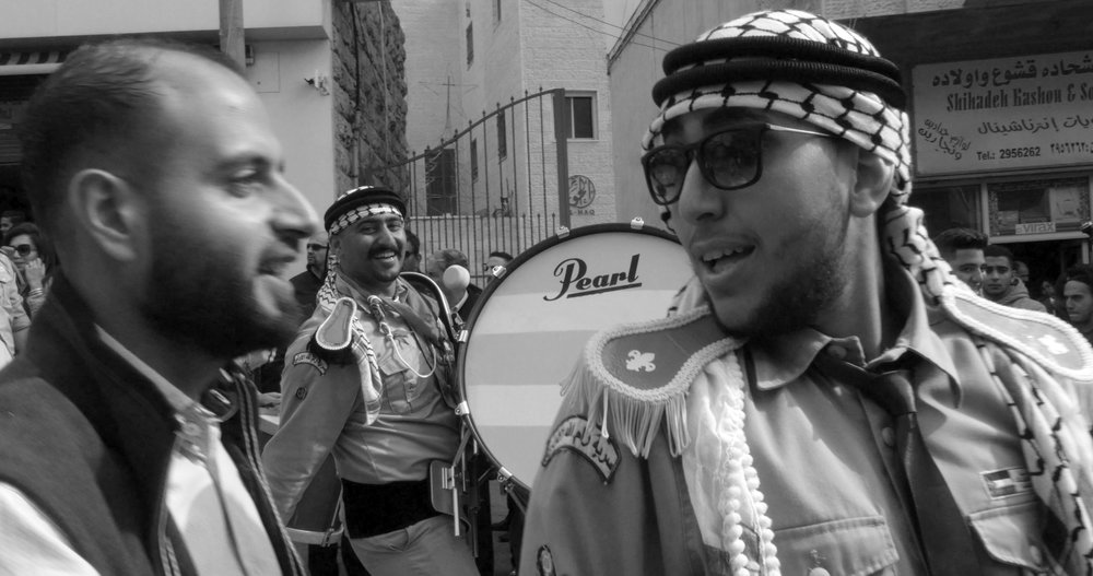 The band-leader smiles to an onlooker at the Easter parade in Ramallah