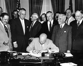 President Eisenhower signing HR7786, changing Armistice Day to Veterans Day. From left: Alvin J. King, Wayne Richards, Arthur J. Connell, John T. Nation, Edward Rees, Richard L. Trombla, Howard W. Watts